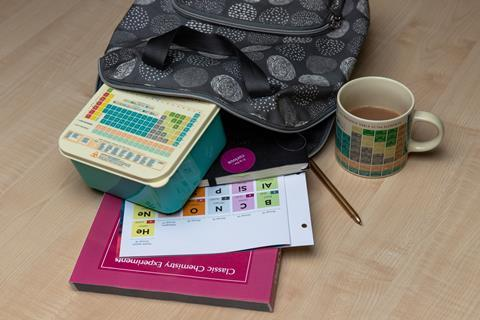 An image showing an open backpack containing a periodic table lunch box, a printed periodic table, a textbook, a notebook and a pen; a mug with the periodic table printed on it can also be seen on the table